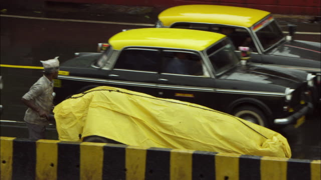 A man pushes a cart covered in a yellow plastic alongside traffic in Mumbai, India. Available in HD.