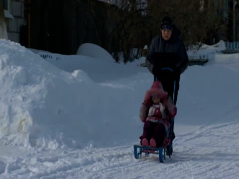 A man pushes a child in a sledge pushchair along a snowy street in the village of Buranovo