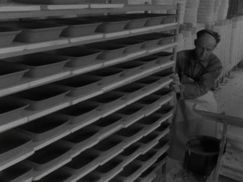 man pushes a rack full of clay dishes next to racks of cups and bowls at the stavanger pottery workshop. 1959. - stavanger stock videos & royalty-free footage