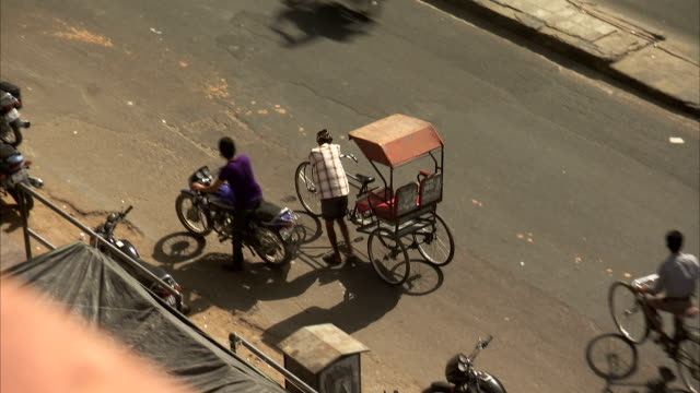 a man pushes a rickshaw along a street in jaipur. available in hd - pushing点の映像素材/bロール