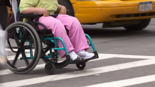 A man pushes a women in a wheel chair across the street