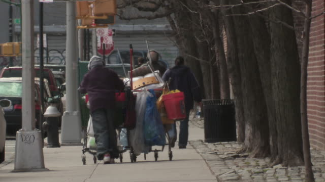 a man pushes all his belongings in a shopping cart on a manhattan street - 住宅問題点の映像素材/bロール