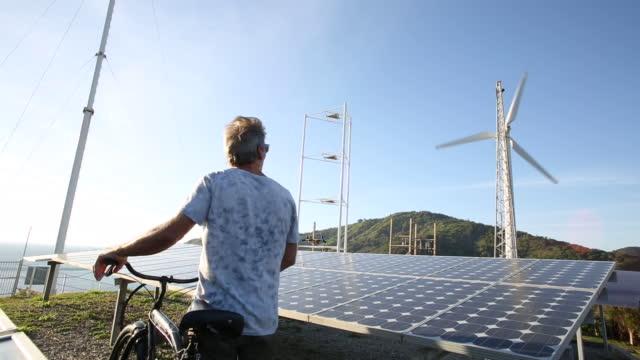vídeos y material grabado en eventos de stock de hombre empuja la bicicleta más allá de los paneles solares, turbina eólica - energía solar