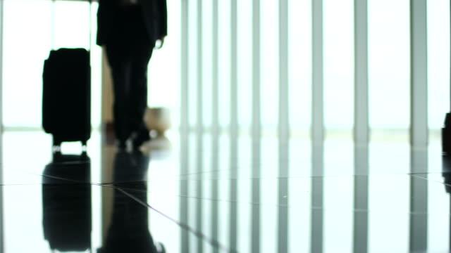 vídeos de stock, filmes e b-roll de man pushes suitcase along glass wall - mala de rodinhas
