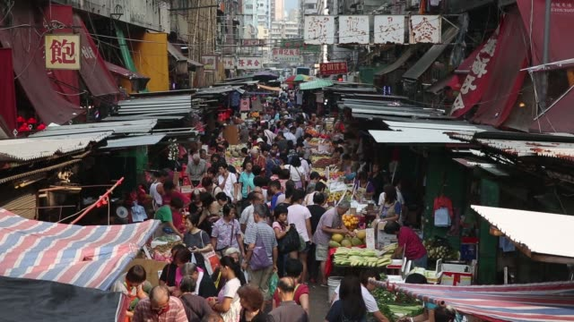 vidéos et rushes de a man pushing a trolley passes fruit and vegetable stalls shoppers buy fruit from a fruit stall in the mong kok district of hong kong china on... - mong kok