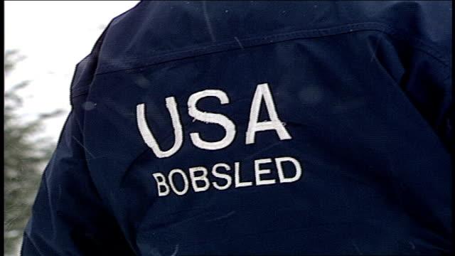 vídeos y material grabado en eventos de stock de man pushing bobsled one wearing usa bobsled team jacket in lake placid ny - usa