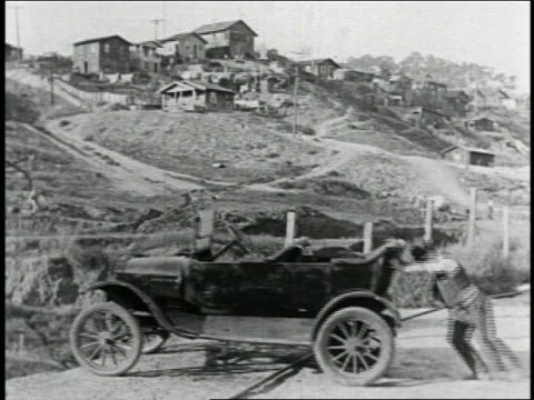 B/W 1925 man (Billy Bevan) pushing car toward edge of cliff / houses + horses in background / feature