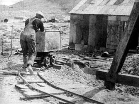b/w 1927 man pushing cart on track then dumping out dirt + rocks at gold mine / nevada / newsreel - gold mine stock videos and b-roll footage