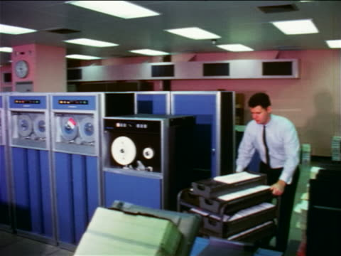 1965 pan man pushing cart past computer tape drives + other workers / documentary - 1965 stock videos & royalty-free footage