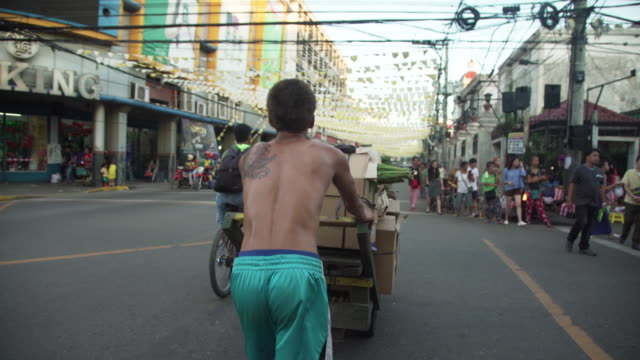 man pushing cart transporting boxes at cebu city street b-roll, philippines - city life stock videos & royalty-free footage