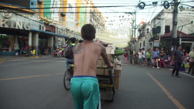Man pushing cart transporting boxes at Cebu city street b-roll, Philippines
