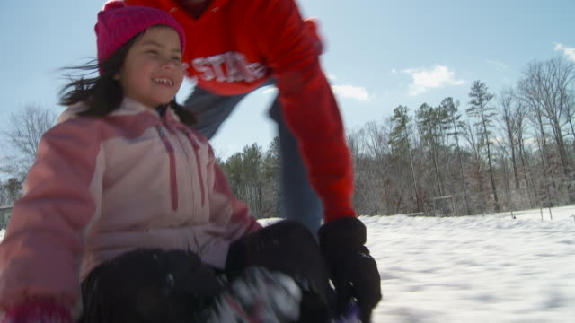 ws man pushing girl (6-7) on sled down snowy hill, richmond, virginia, usa - richmond virginia stock videos & royalty-free footage