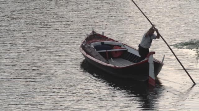 WS Man pushing gondola off shore / Florence, Italy