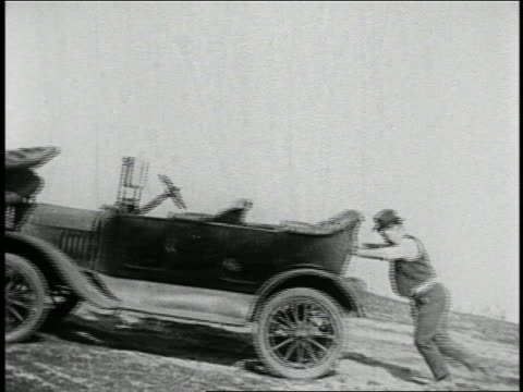 b/w 1925 man (billy bevan) pushing group of cars bumper to bumper up steep hill / feature - anno 1925 video stock e b–roll