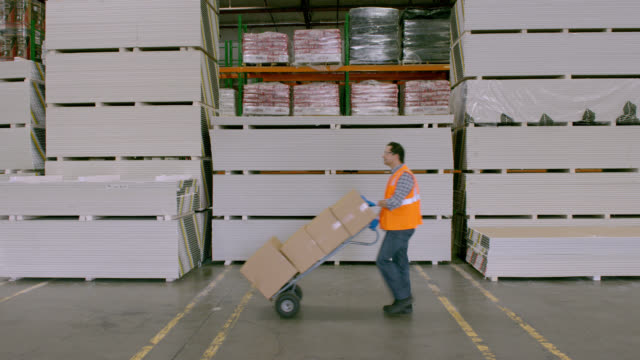 PAN man pushing hand truck stacked with boxes in warehouse; crosses frame right to left