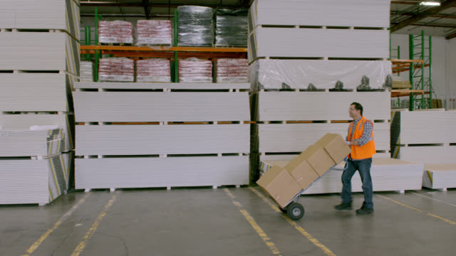 PAN man pushing hand truck stacked with boxes in warehouse; enters frame right, exits frame left