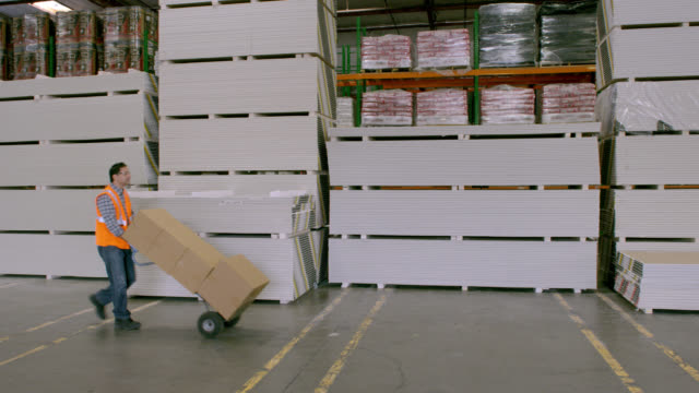 PAN man pushing hand truck stacked with boxes in warehouse; enters frame left, exits frame right