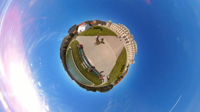 man pushing his bike around a tiny planet at  at belvedere castle in vienna - 360° time lapse - traditionally austrian stock videos & royalty-free footage