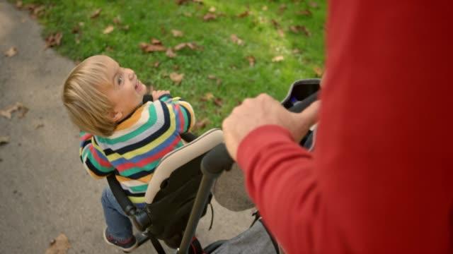 vídeos y material grabado en eventos de stock de slo mo hombre empuja a su hijo en un triciclo a través de un camino soleado por un parque - abuelo