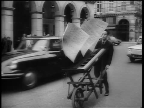 vidéos et rushes de b/w 1964 man pushing piano with large sheets of music tacked on in paris street / france / newsreel - partition musicale