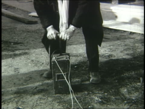 B/W 1953 man pushing plunger to detonate explosion