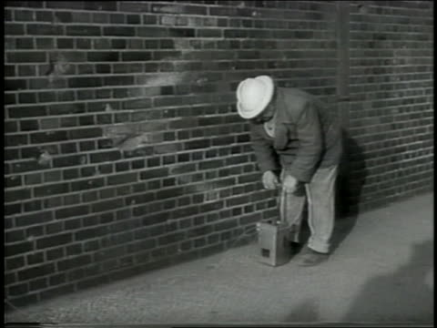 B/W 1959 man pushing plunger to detonate explosives / Berlin