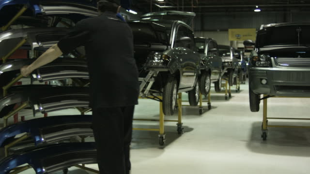 ws man pushing rack of bumpers to electric car on production line, attaching bumper onto front of electric car, st. jerome, quebec, canada - bumper stock videos & royalty-free footage
