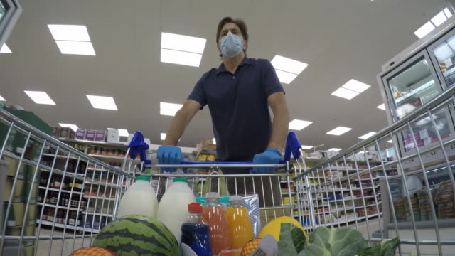 man pushing supermarket trolley wearing protective mask and gloves - full stock videos & royalty-free footage