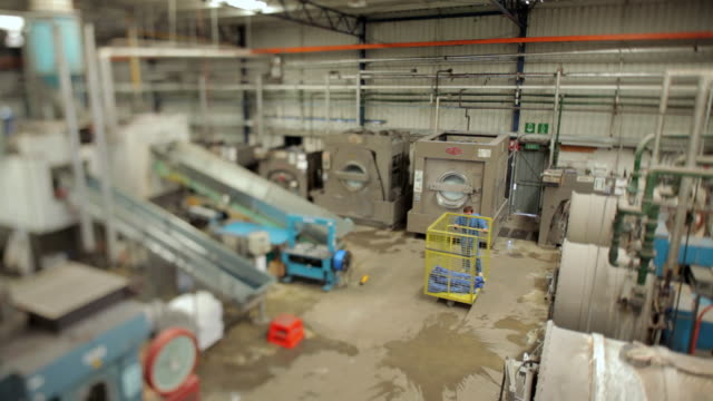 vídeos de stock e filmes b-roll de ws man pushing trolley full of blue hand towels through factory / perth, western australia, australia - só um homem de idade mediana
