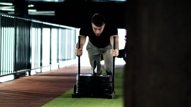 vídeos de stock e filmes b-roll de man pushing weight sled in the gym - empurrar atividade física