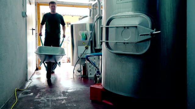 man pushing wheelbarrow in brewery - wheelbarrow stock videos and b-roll footage