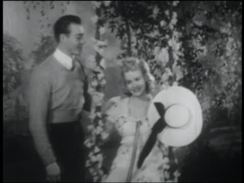 b/w 1941 man pushing woman on flowered swing outdoors - romance stock videos & royalty-free footage