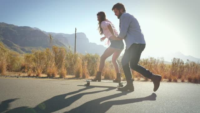 vídeos y material grabado en eventos de stock de man pushing woman on skateboard - adulto de mediana edad