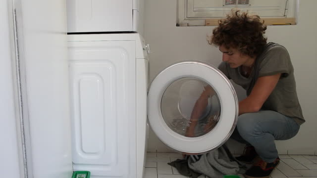 vídeos y material grabado en eventos de stock de man put clothes in the washing machine - un solo hombre joven