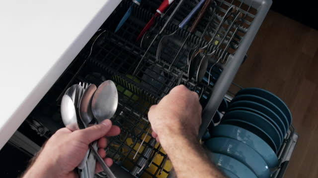 man put spoon in a dishwasher - lavastoviglie video stock e b–roll