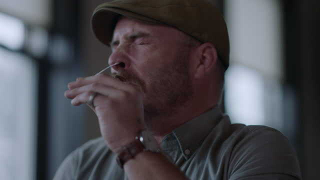 stockvideo's en b-roll-footage met cu man puts a cotton swab uncomfortably far up his nose - testkit