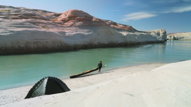 ws a man puts a kayak into the water at lake powell - lago powell video stock e b–roll