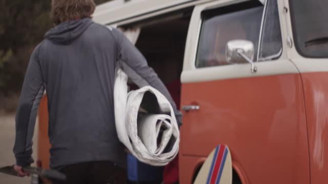 vídeos de stock e filmes b-roll de man puts deflated paddleboard in van, slow motion - carrinha veículo