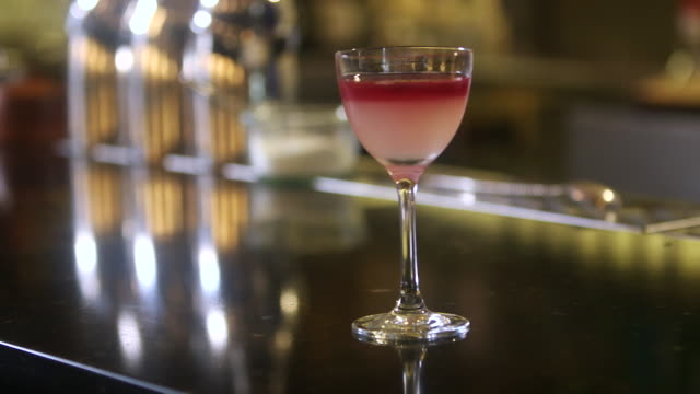 stockvideo's en b-roll-footage met cu man puts down pink cocktail on table / united states - martiniglas