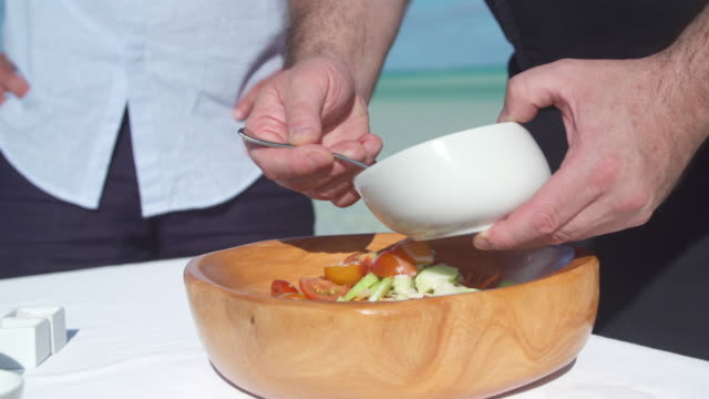 a man puts dressing on a poke salad lunch in a bowl. - territori francesi d'oltremare video stock e b–roll