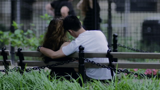 A man puts his arm around a girl as they sit on a park bench.