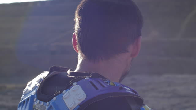 stockvideo's en b-roll-footage met a man puts his helmet on his head for motocross motorcycles on a dirt off road. - slow motion - men