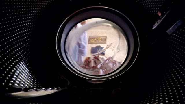 man puts his shirts into the washing machine. - hygiene stock videos and b-roll footage