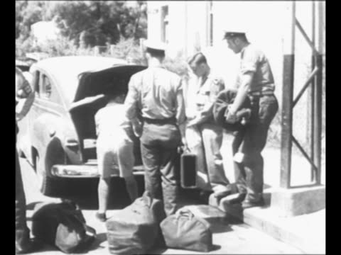 man puts luggage into trunk of car as un guards stand by in preparation for un truce team departure from palestine / military truck approaches passes... - 1948 stock videos & royalty-free footage