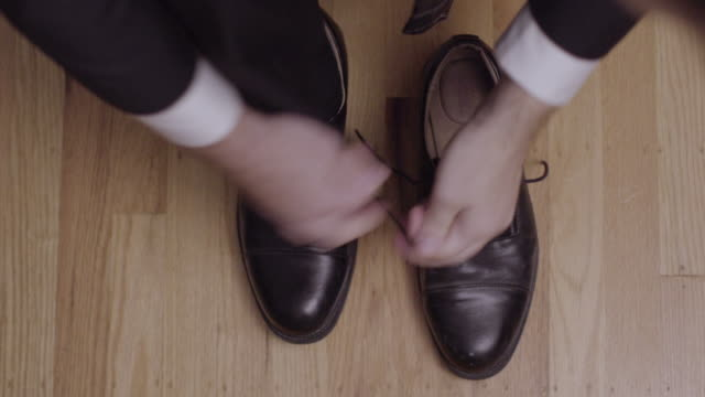 a man puts on a pair of dress shoes - dress shoe stock videos and b-roll footage