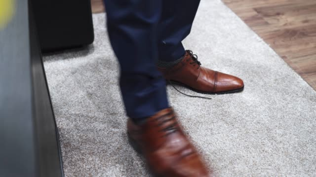Man puts on brown leather shoes and ties up shoelaces on them