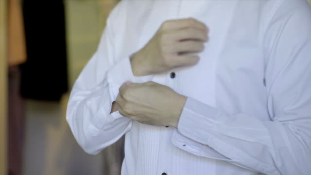 Man Puts on cufflinks