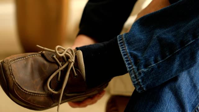 Man Puts on Shoe