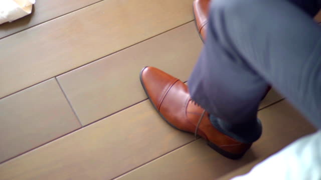 vídeos de stock, filmes e b-roll de homem coloca sapatos - laço acessório