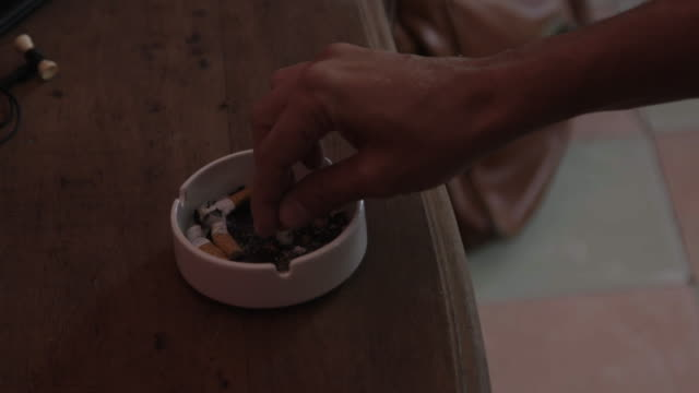 Man puts out cigarette in ashtray, slow motion close up